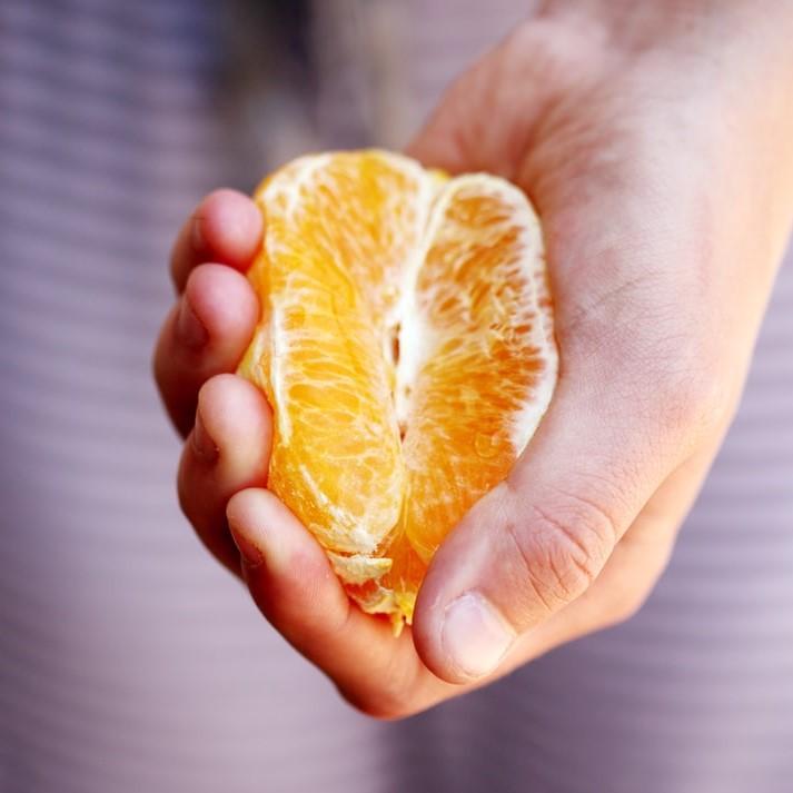 Сжатый в руке апельсин